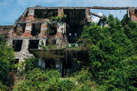 Overgrown ruins of abandoned school with bullet marks, consequences of war in Abkhazia.