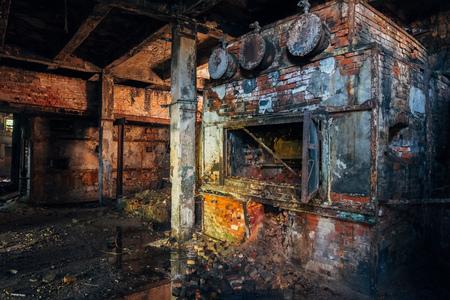Old brick industrial stove in abandoned boiler room in derelict factory.