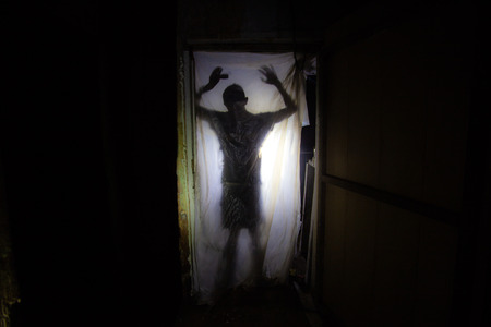 Human silhouette behind packing film in dark creepy room of abandoned building.