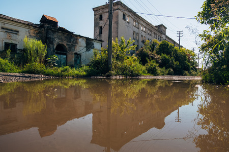 Abandoned buildings reflected in pool of rainwater.