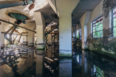 Flooded abandoned ruined flour mill factory. Old rusty pipes in dirty water.