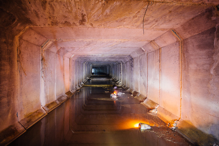 Flooded rectangular sewer tunnel with dirty urban sewage illuminated by color lights and candles Foto de archivo