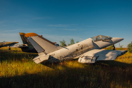 Abandoned broken old Soviet military fighter airplanes on grassy ground.