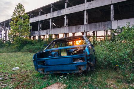 Coche destrozado y edificio industrial en ruinas abandonado en el fondo del atardecer.