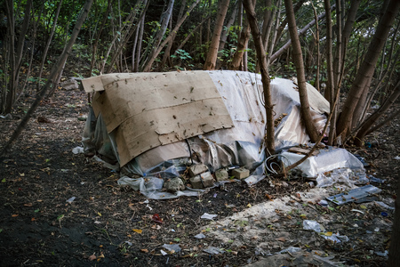 Homeless doweling. Small habitation, tent made from garbage in dirty littered forest