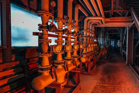 Steel industrial pipeline with valves and manometers in corridor of abandoned factory.