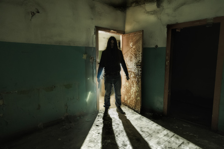Serial killer maniac with knife in dark abandoned building. Maniac thriller concept. Stock Photo
