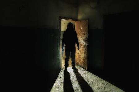 Espeluznante silueta de hombre desconocido con cuchillo en oscuro edificio abandonado. Horror sobre el concepto maníaco.