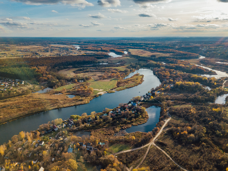 Aerial view of rural landscape in autumn. Small village houses, river, autumn trees, farm fields from drone point of view.