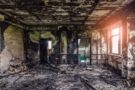 Burned interiors after fire in industrial or office building. Walls and staircase in black soot Archivio Fotografico