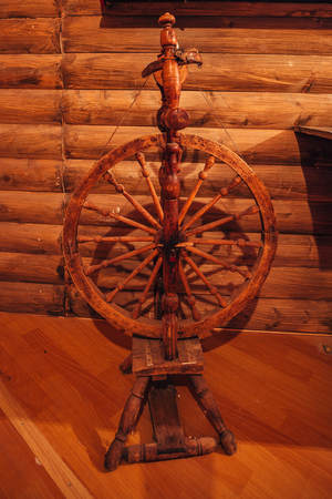 Old traditional Russian spinning wheel in village house.