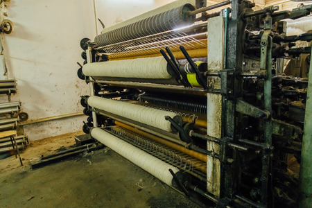 Wool thread production line. Spinning machinery with spindles and wool yarns.