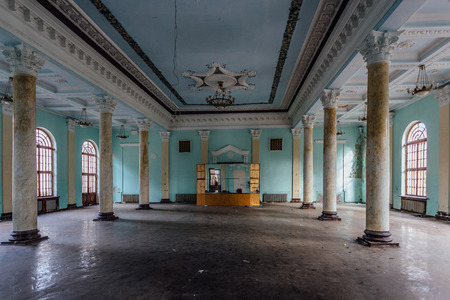 Interior of large column hall with fretwork at abandoned mansion.