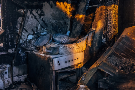 Burnt house interior. Burned kitchen, remains of stove and furniture in black soot. Stock Photo