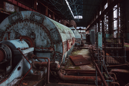 Rusty turbine generator. Abandoned destroyed by war and overgrown by plants and moss machinery of Tkvarcheli (Tquarchal) power plant, Abkhazia, Georgia.
