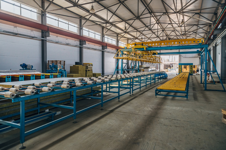 Modern thermal insulation sandwich panel production line. Machine tools, roller conveyor and overhead crane in workshop.
