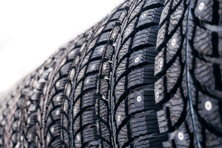 Clean new modern studded winter tires in row. Tires with spikes, close up, isolated.