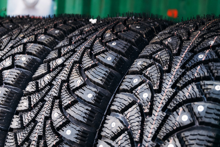 Clean new modern studded winter tires in row. Tires with spikes, close up. Stockfoto