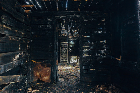 Completely burnt wooden house. Consequences of fire.