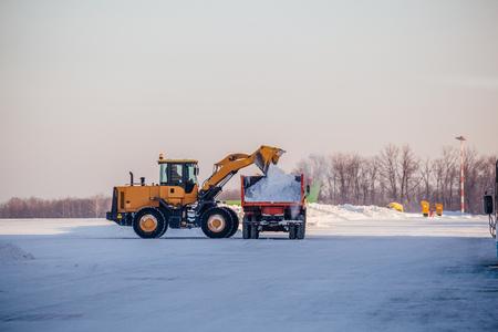 Pulizia della neve in aeroporto. L'escavatore carica la neve nell'autocarro con cassone ribaltabile.