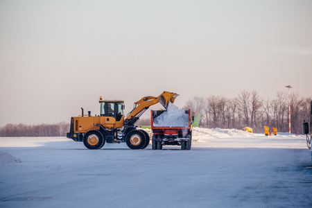 Snow cleaning in airport. Excavator loads snow into dump truck. Zdjęcie Seryjne