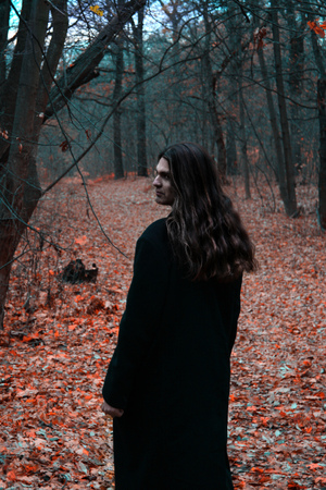 Brutal depressive Gothic stylish long haired man in autumn forest.