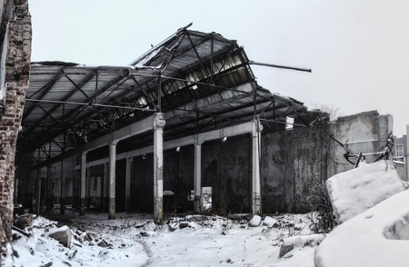 Ruined by war or other disaster industrial building in foggy winter. Stockfoto