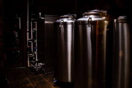 Small private brewery. Industrial stainless steel fermentation vats Imagens