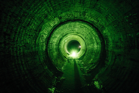 Flooded round underground drainage sewer tunnel with dirty sewage water green illuminated. 스톡 콘텐츠 - 116867549