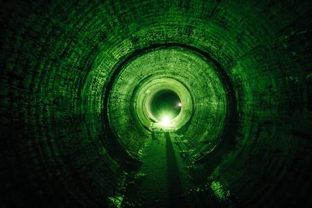 Zalany okrągły podziemny tunel kanalizacyjny z brudnymi ściekami oświetlony na zielono.
