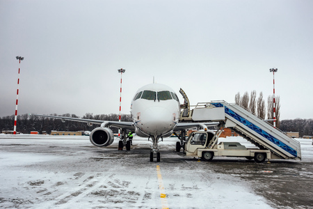 Landed white passenger airplane with attached ladder in winter airport, rear view Imagens