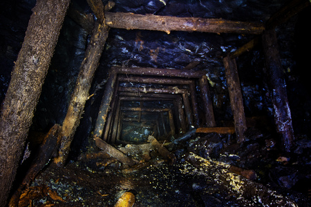 Abandoned mine with rotten wooden miner stands. Old derelict development in coal field.