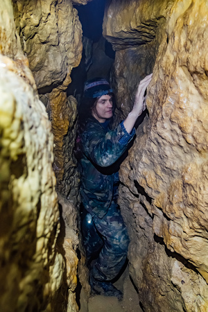 Man explores narrow passage in cave
