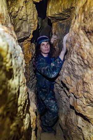 Man explores narrow passage in cave