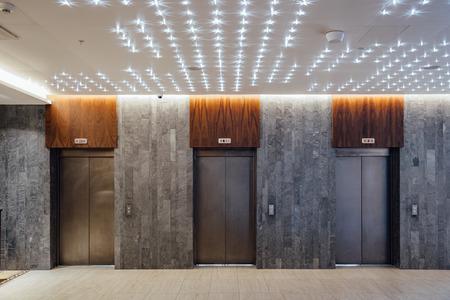 Three closed elevators in modern hotel lobby.