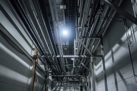 Heating or cooling water pipes on ceiling of industrial or office building. Stock Photo