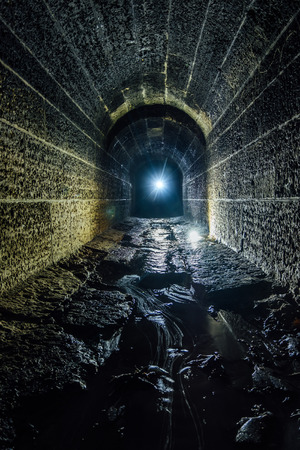 Old vaulted flooded underground drainage sewer tunnel with dirty sewage water