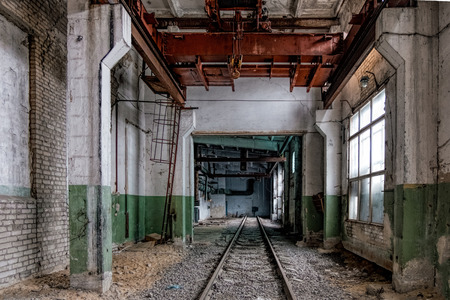 Abandoned empty train depot with old rusty bridge crane.
