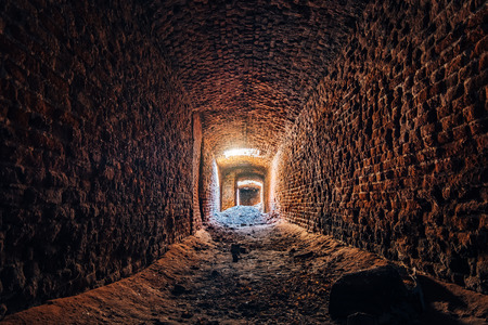 Old underground ruined red brick historical vaulted tunnel. Banco de Imagens