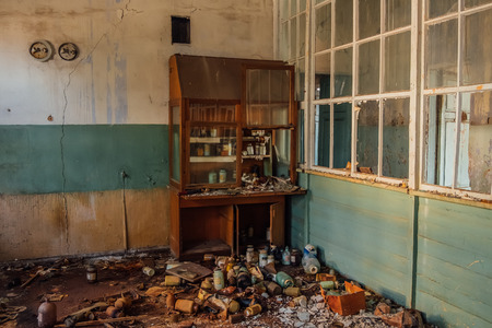 Old cabinet with broken glassware in abandoned chemical laboratory