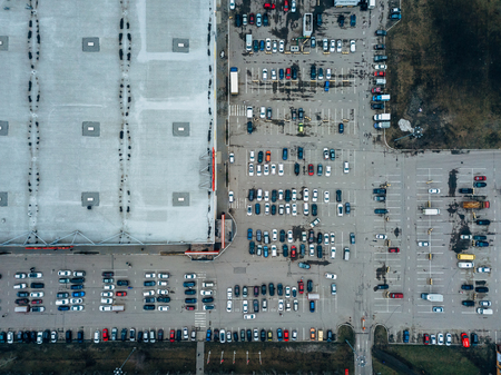 Top view of parking lot near large trade center taken by drone.