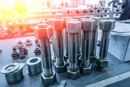 Große Schrauben mit eingeschraubten Muttern in der Metallverarbeitungsfabrik. Standard-Bild
