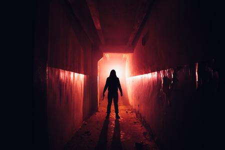 Siluetta raccapricciante con coltello nell'edificio abbandonato illuminato rosso scuro. Orrore per il concetto di maniaco.