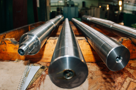 New steel shafts in factory, close up, selective focus.