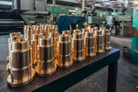 New brass threaded bushings on table in factory.