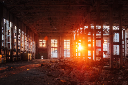 Sunlight of sunset in large abandoned industrial building of Voronezh excavator factory.