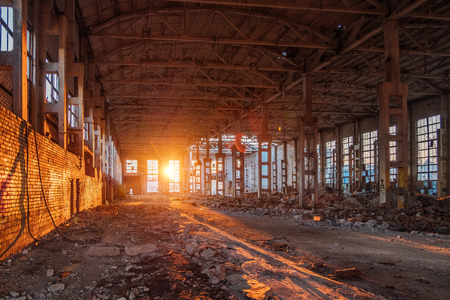 La luz del sol del atardecer en el gran edificio industrial abandonado de la fábrica de excavadoras Voronezh.
