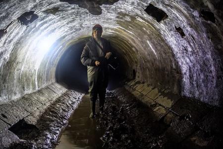 Sewer worker in underground sewer tunnel Stockfoto