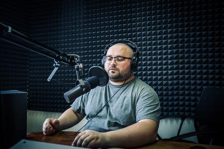 Talking male radio presenter in radio station. Stock Photo