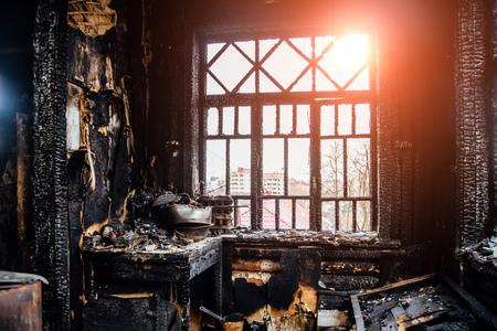 Burnt house interior. Burned kitchen, remains of furniture in black soot. Banco de Imagens